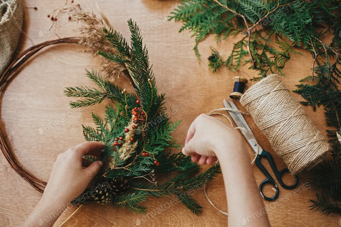 Hands holding fir branches and pine cones, berries, thread, scissors on wooden table