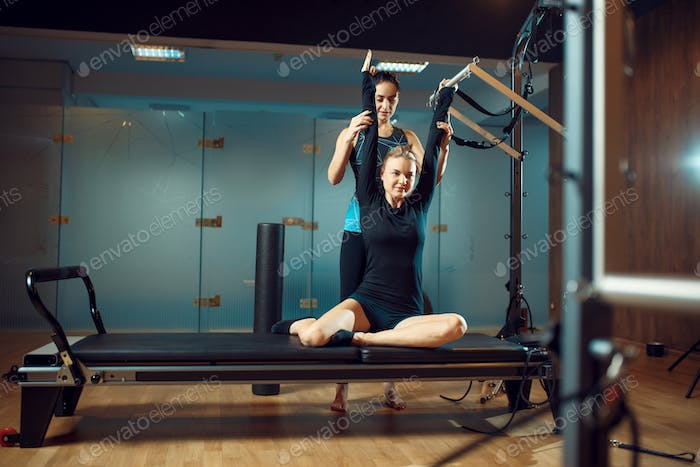 Girl and instructor, pilates training in gym
