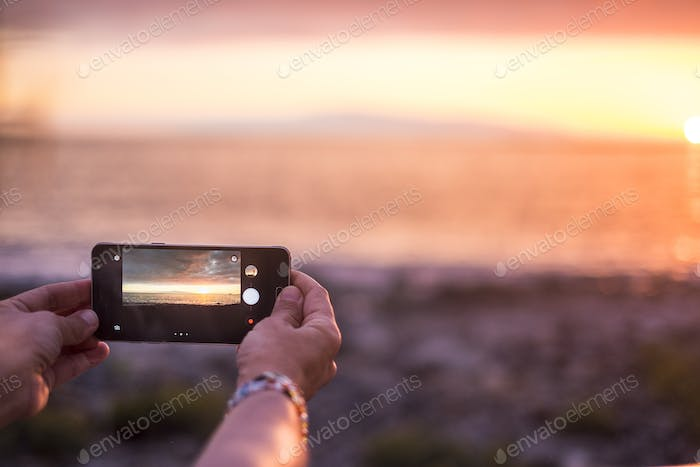 woman take picture of the sunset at the ocean in summer vacation