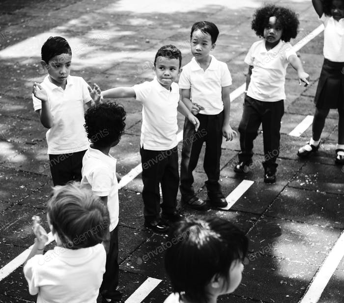 Group of diverse kindergarten students standing in line at playg