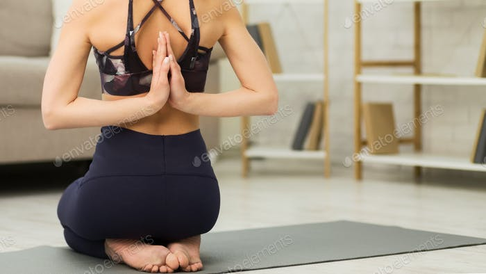 Sporty woman doing yoga and holding hands behind back