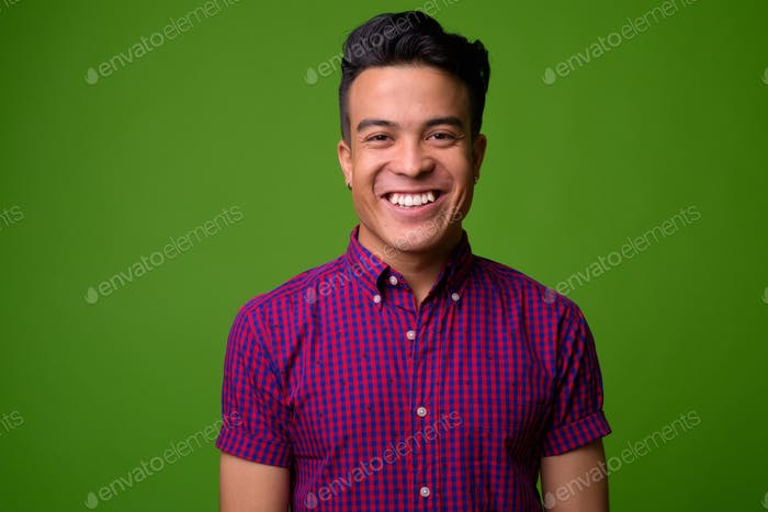 Young multi-ethnic man wearing purple shirt against green background