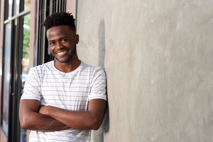 attractive young african man leaning on wall with arms crossed