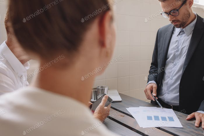 Male executive explaining a financial plan to coworkers