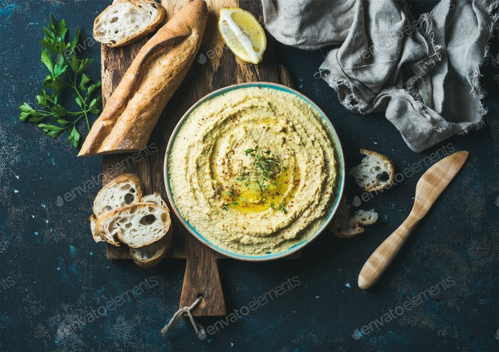 Homemade hummus with lemon, herbs and freshly baked baguette