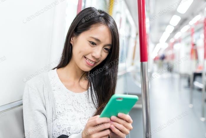 Frau Gebrauch von Handy und unter MTR in Hong Kong