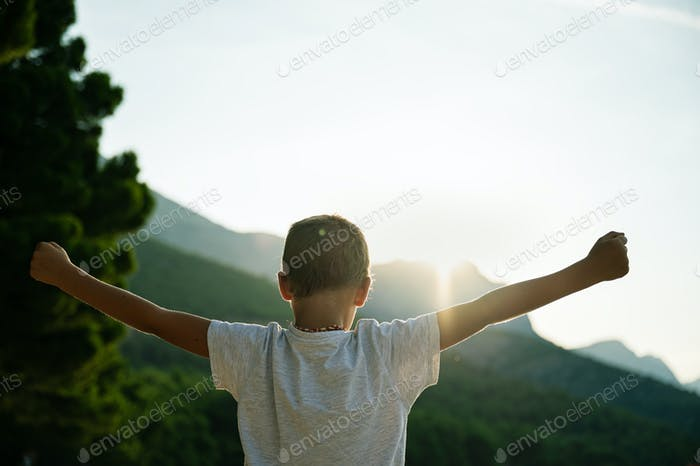 Young boy standing outside at sunrise
