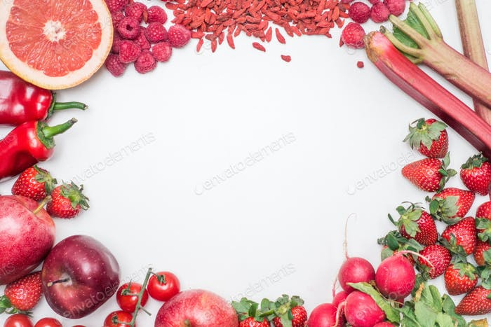 Aerial vibrant shot of red fruit and vegetables on a white background