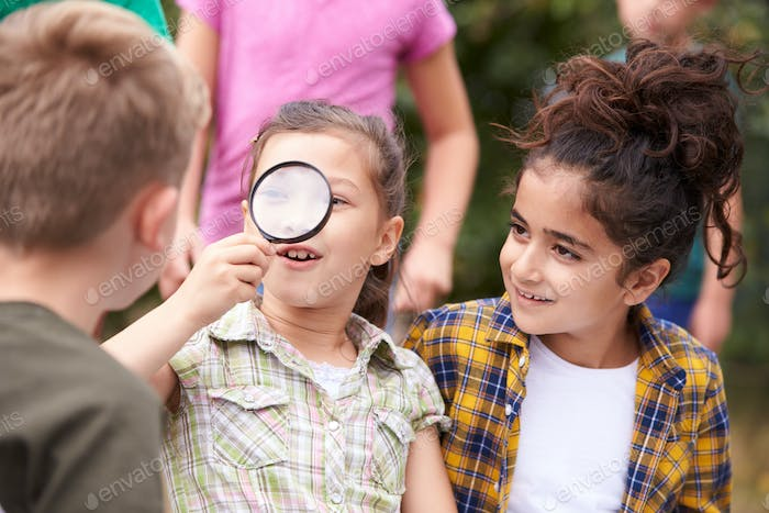 Group Of Children On Outdoor Activity Camping Trip Looking At Map Together