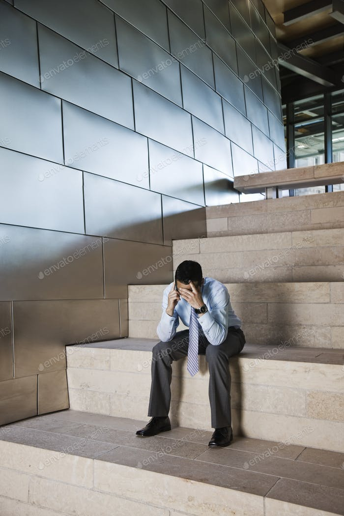 Businessman in a stressful situation while on a cell phone in the lobby of a large office building.