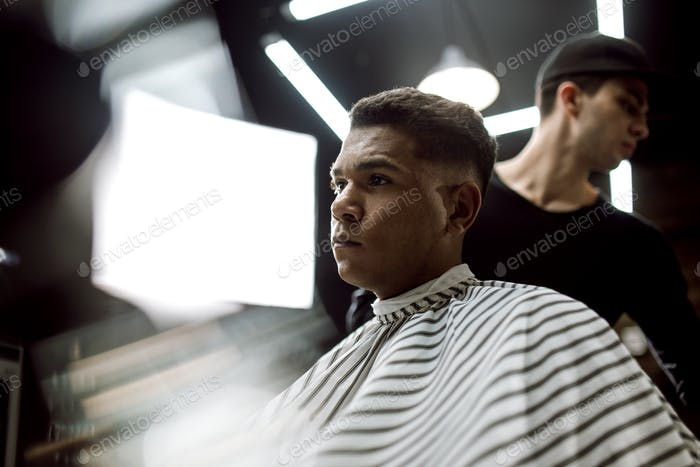 The fashion barber in black clothes makes a razor cut hair for a stylish black-haired man sitting in