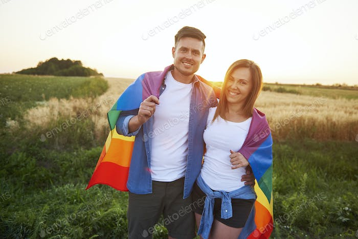 Portrait of smiling young couple with  rainbow flag