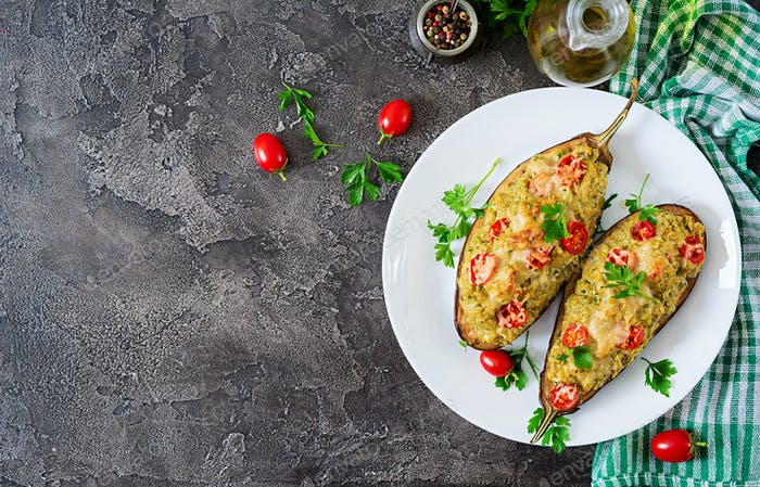Minced meat chicken and vegetables stuffed eggplants on a grey background.
