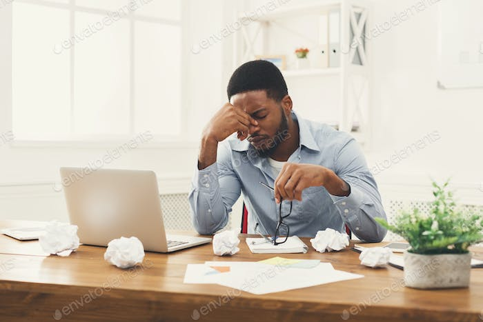 Overworking african-american employee at workplace