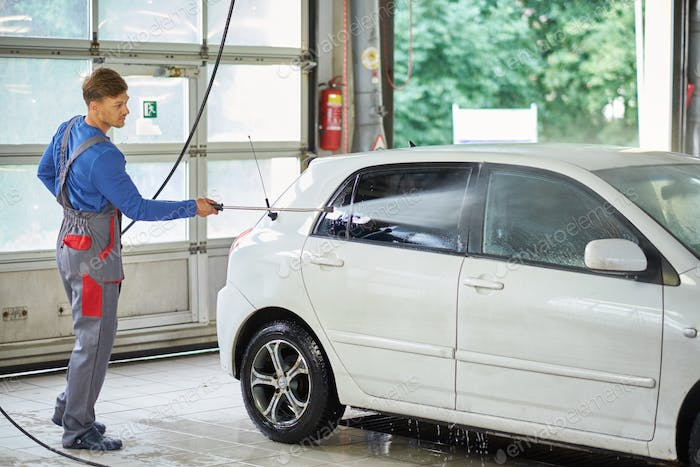 Man worker washing car on a car wash