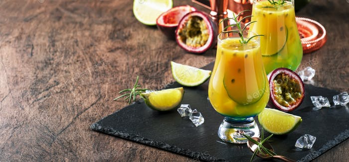 Passion fruit cocktail with rosemary and ice cubes in glass