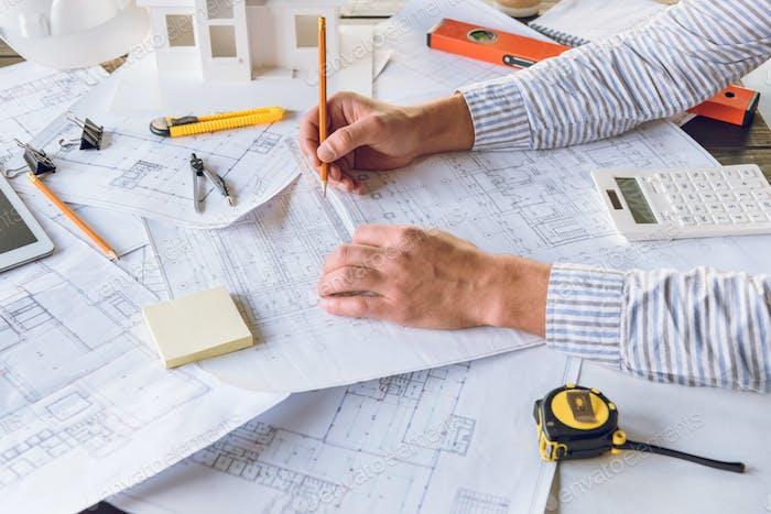Teilansicht des Architekten, der mit Entwürfen für neue Gebäudeentwurf arbeitet