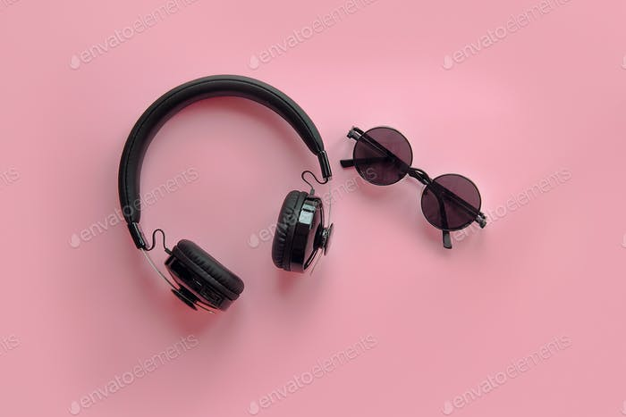 Black sunglasses and headphones on pink background
