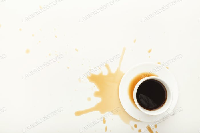 Coffee cup and spilt espresso on white background