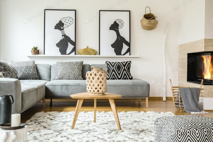 Wooden table on carpet in african living room interior with patt