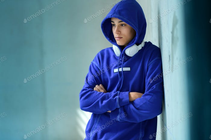 Thoughtful serious teenage boy in a blue hoodie
