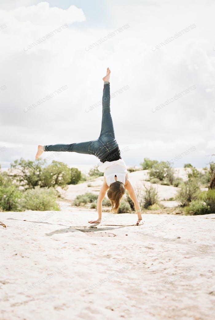 Barefoot woman wearing jeans, cartwheeling