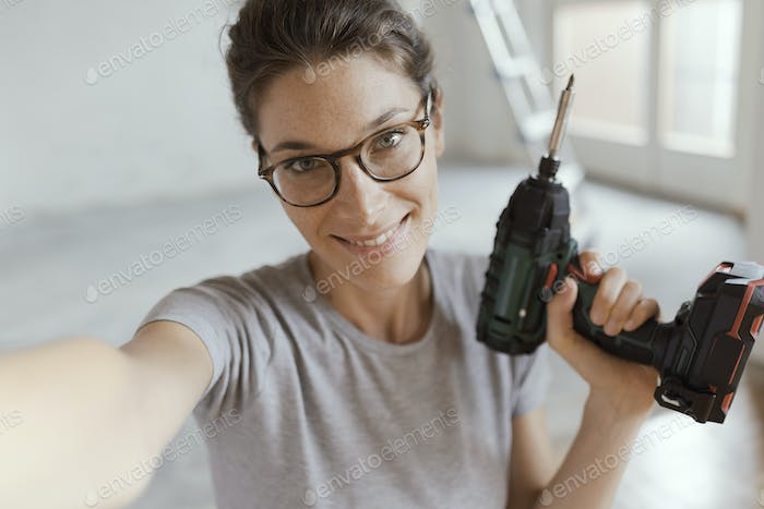 Cheerful woman holding a drill and taking a selfie
