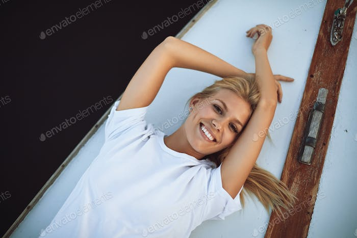 Smiling young woman lying on the deck of a yacht