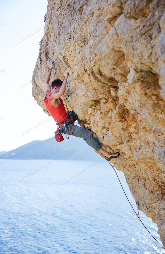 Young man lead climbing on overhanging cliff