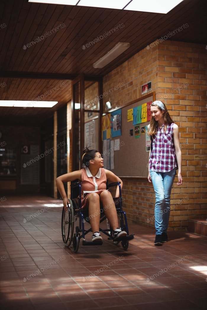 Schoolgirl talking with her disabled friend in corridor