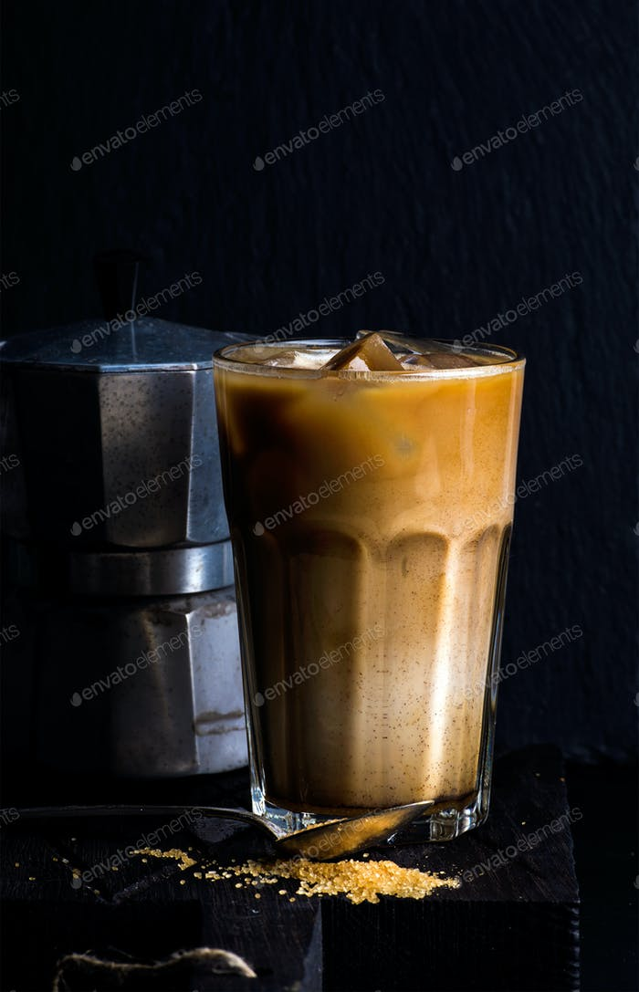 Iced coffee with milk in a tall glass, moka pot, black background