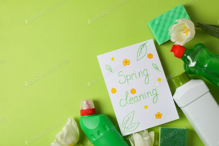 Text Spring cleaning, cleaning tools and tulips on green background