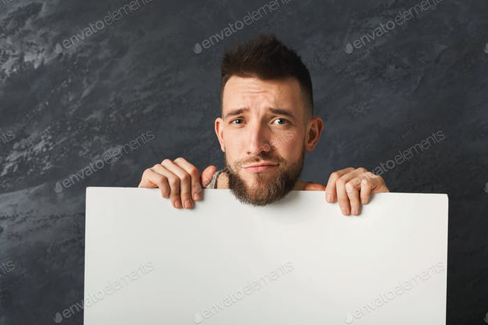 Handsome sad man holding white paper in studio