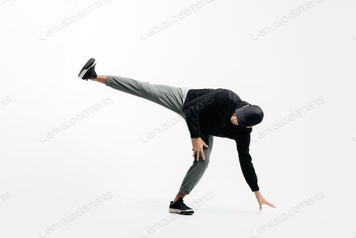 Schöner junger Mann trägt ein schwarzes Sweatshirt, graue Hose und eine Mütze tanzt Breakdance