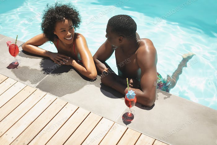 happy young African American couple leaning on edge of swimming pool in their backyard
