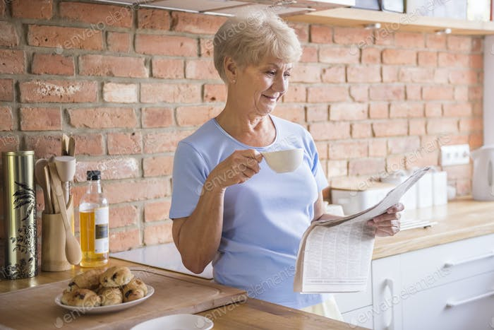 Senior woman reading newspaper in the kitchen