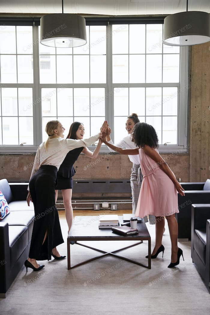 Female colleagues high five at a casual meeting, vertical