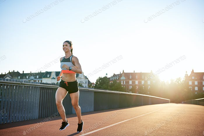 Cheerful woman running along city bridge