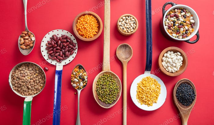 Top view of fflat lay of assortment of legumes on red tabletop background, in scoop and ladles.