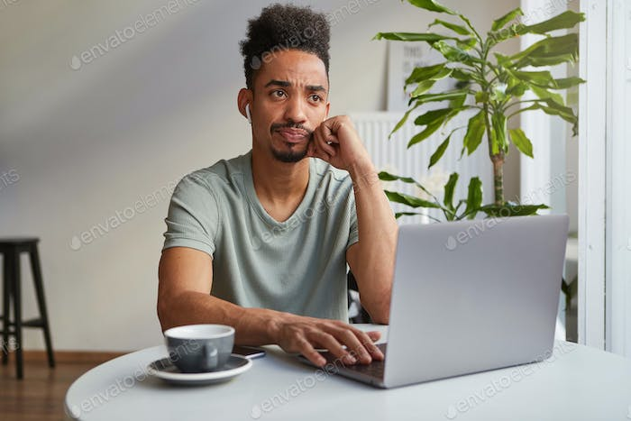 Portrait of frowning young attractive African American thinking boy, sits in a cafe works at laptop