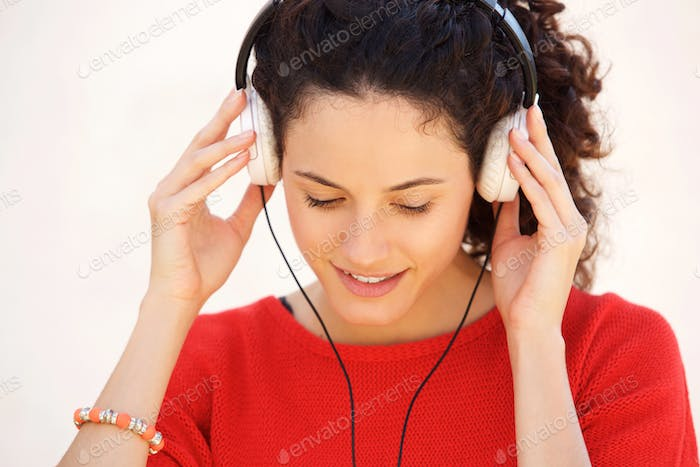 Close up young woman listening to music with headphones against