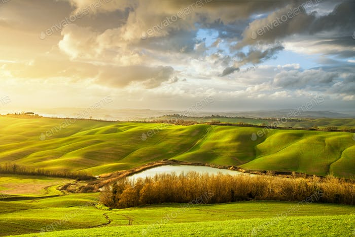 Tuscany misty panorama at sunset, rolling hills, lake, fields, m