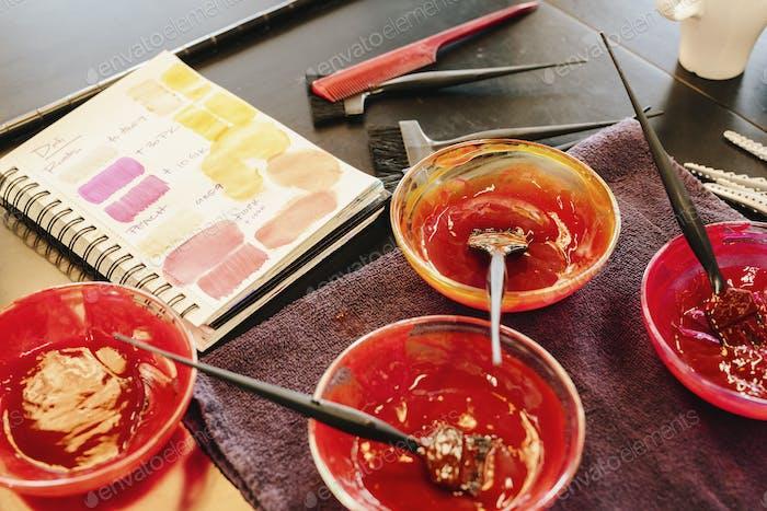 Macetas de color de pelo y una carta de colores en una peluquería.