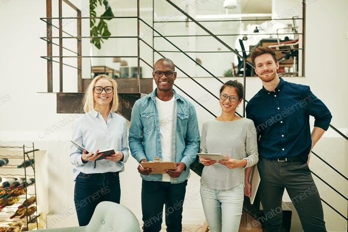 Diverse businesspeople smiling while standing together in a modern office
