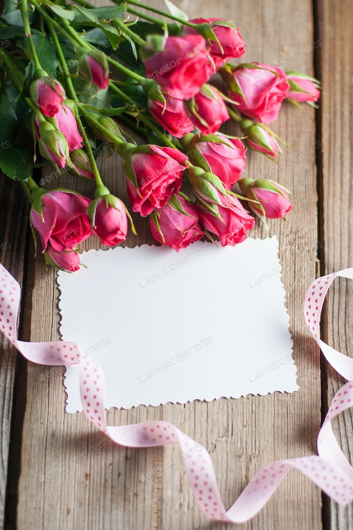 Pink roses and white card with a place for a text on a wooden table