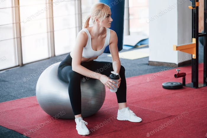 View of beautiful young woman looking away while sitting on exercise mat at gym