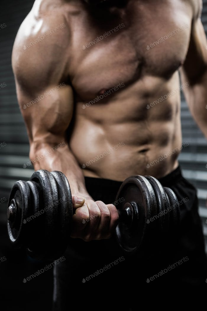 Mid section of shirtless man lifting heavy dumbbell at the crossfit gym