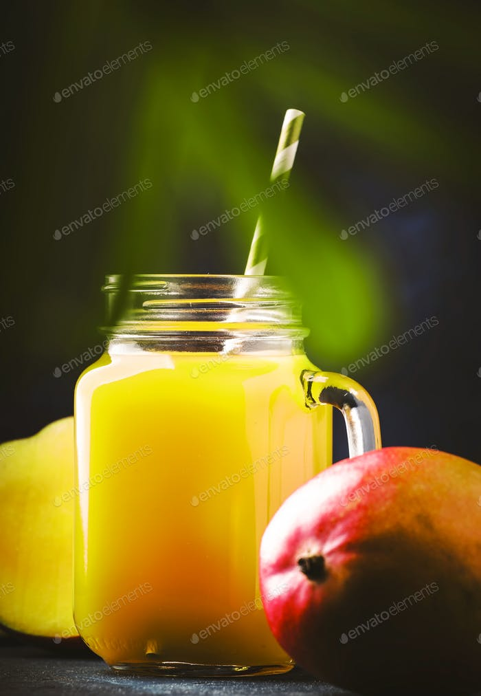 Mango smoothie or cocktail in glass jar with fresh fruit