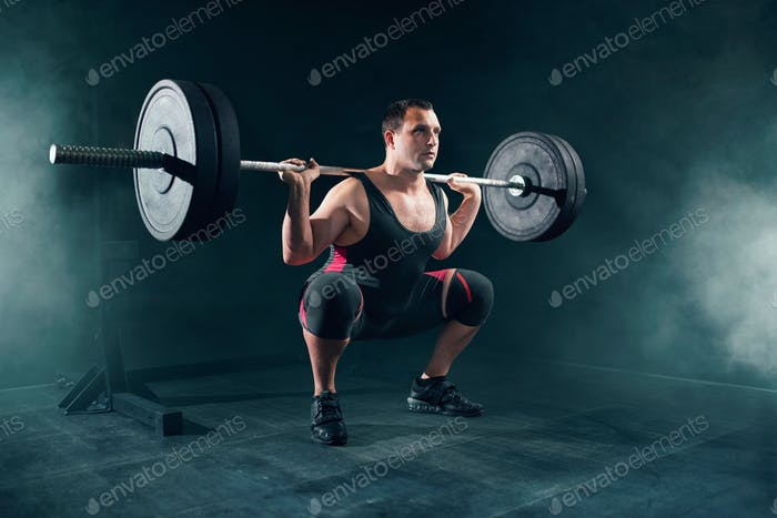Powerlifter in sportswear doing squat with barbell