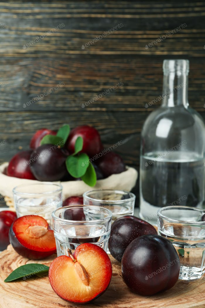 Concept of alcohol with plum vodka against wooden background
